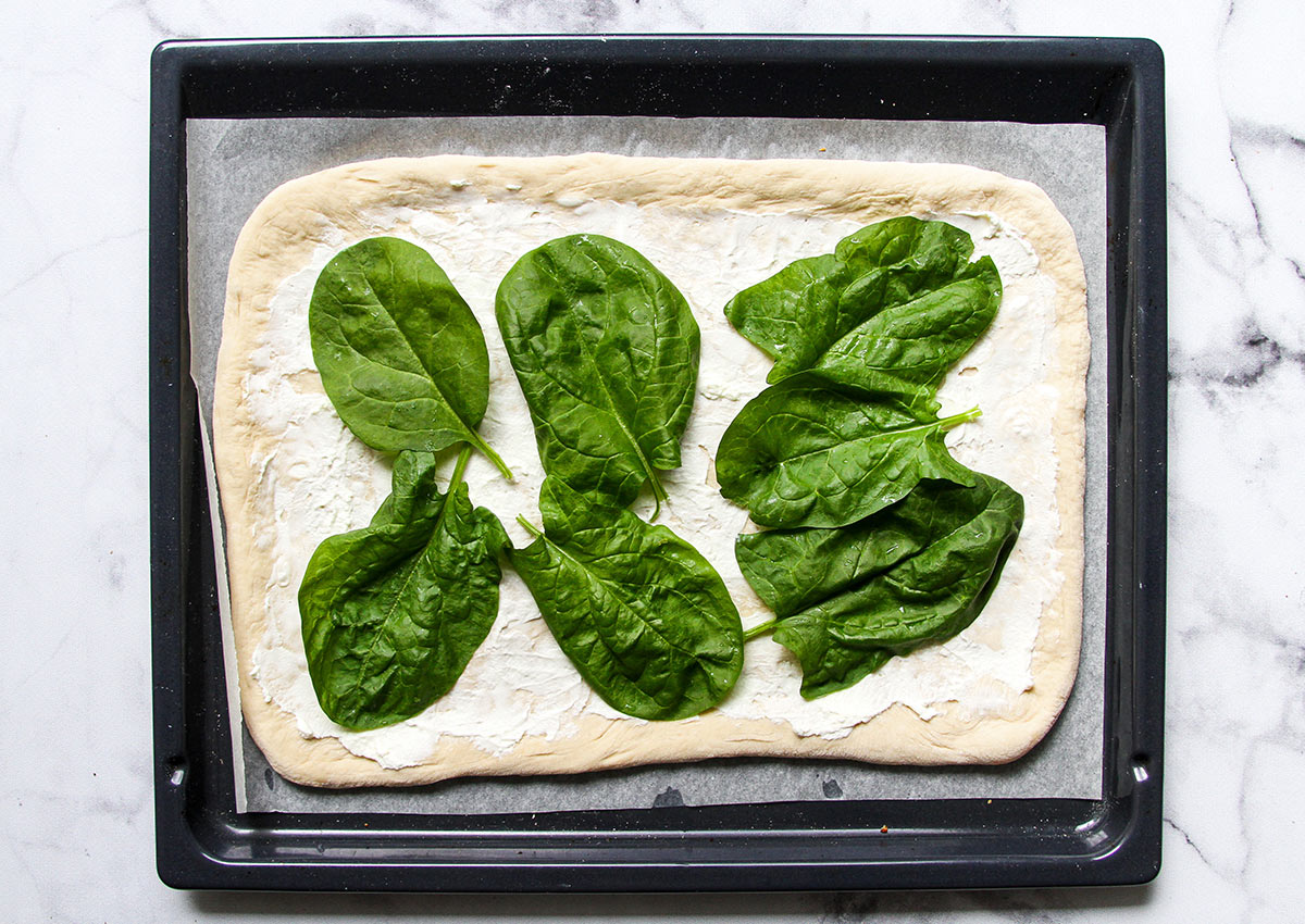 White pizza topped with spinach